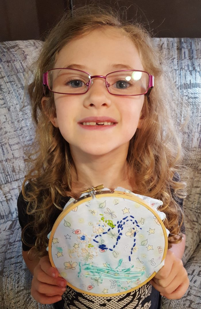 Progeny Press Review girl in glasses showing her handmade story quilt patch she stitched