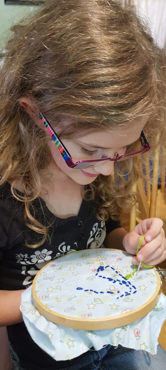 Progeny Press Review girl with glasses sewing a story quilt patch with needle and embroidery floss