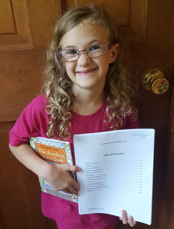 Progeny Press Review girl in glasses and curly hair holding book and study guide
