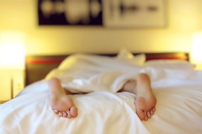 Better night's sleep image person's feet sticking out of the blankets in bed