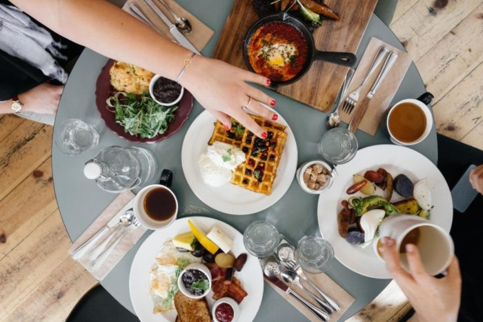 Save money on dining food dishes drinks at a restaurant table hand reaching for waffle plate