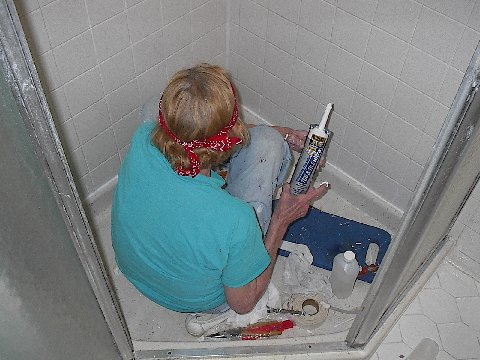 Easy Home Fixes person putting caulk in shower stall
