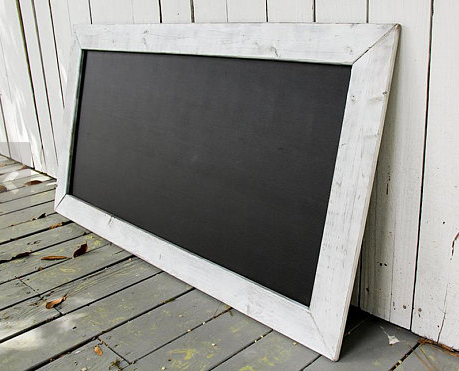 Unique home decor chalkboard that is magnetic sitting on a porch outside
