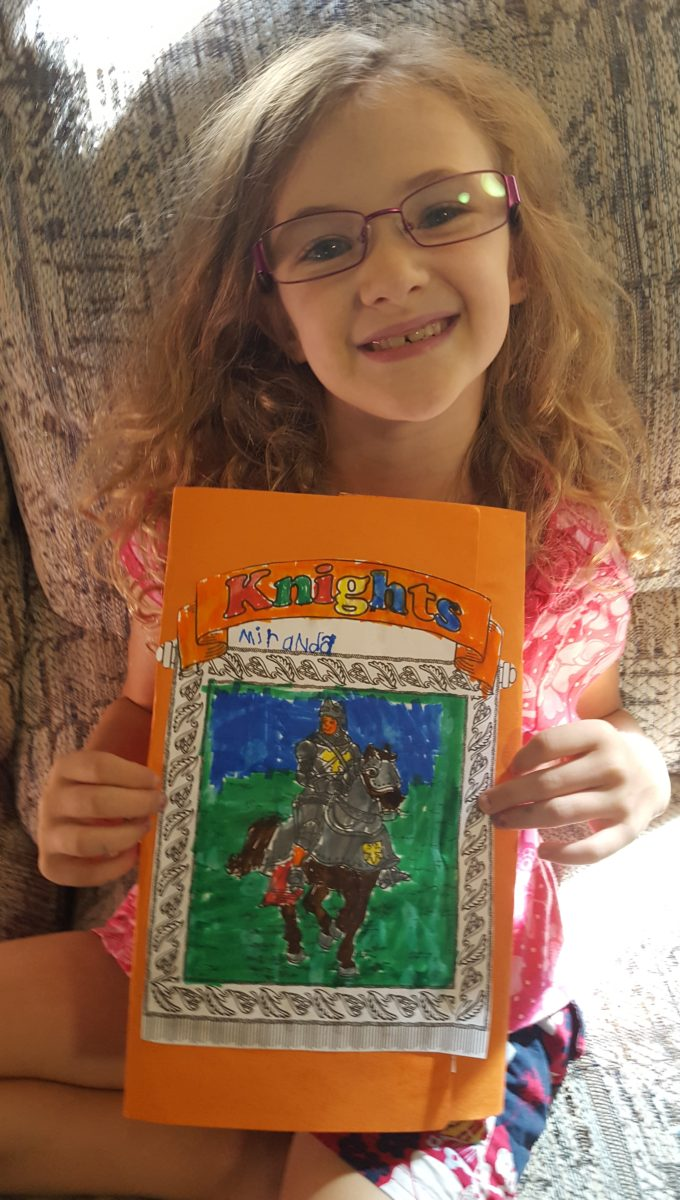 Girl showing her homeade History lap pack with the Knights cover from Homeschool in the woods