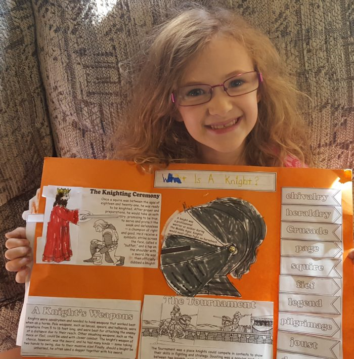 Girl proudly showing her Knights lap-pak from Homeschool In The Woods Publishing