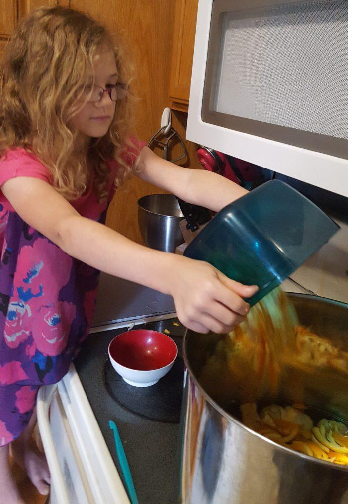 Paddington Bear Literature Based Unit Study girl dumping cut orange peels into pot of marmalade mixture