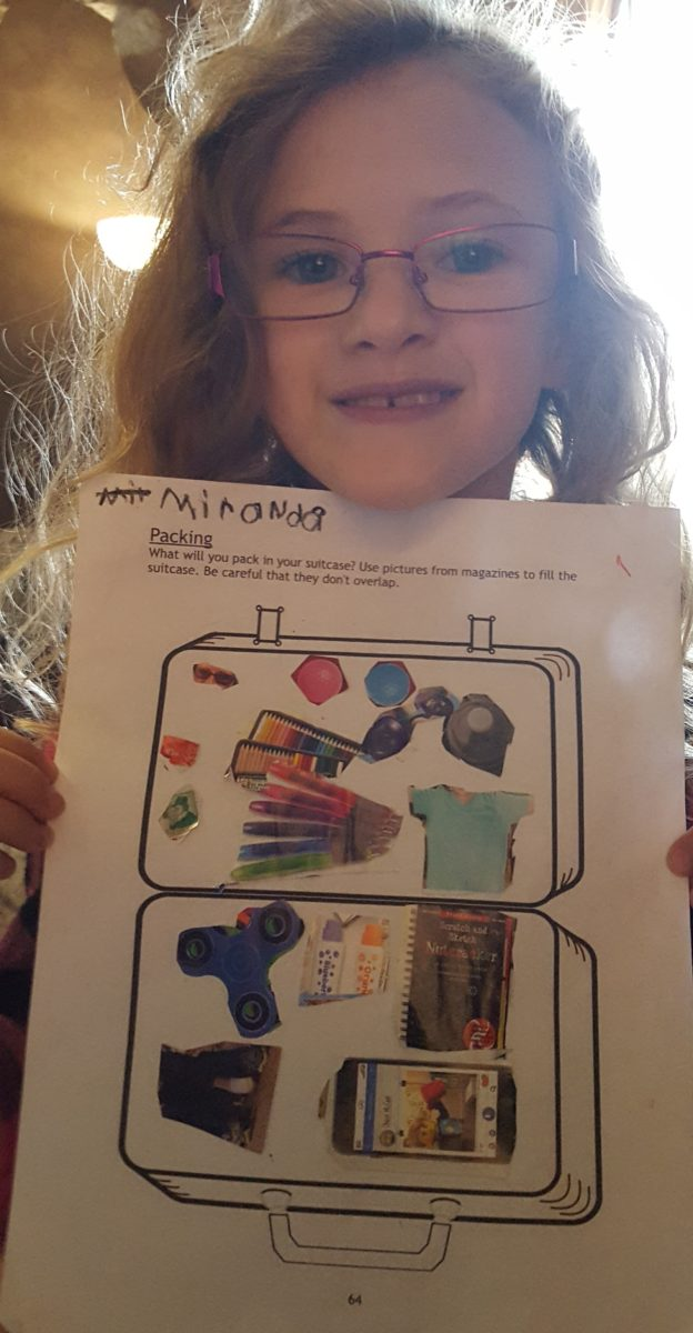 Paddington Bear Literature Based Unit Study girl holding her page of what she would pack if traveling