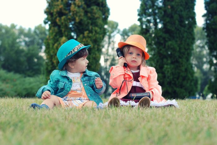 Skills to teach young children - two toddler girls sitting in the grass with a telephone and hats