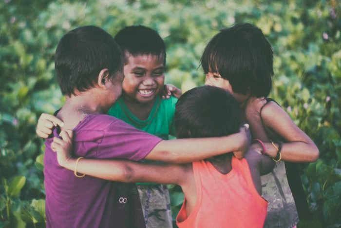 Skills to teach young children four children embrace in friendship after a teamwork session