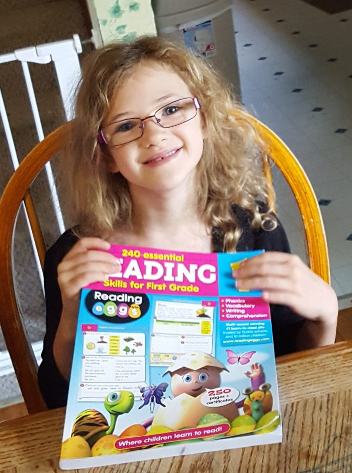 Reading Eggs workbook review first grade second grade girl in glasses smiling holding workbook