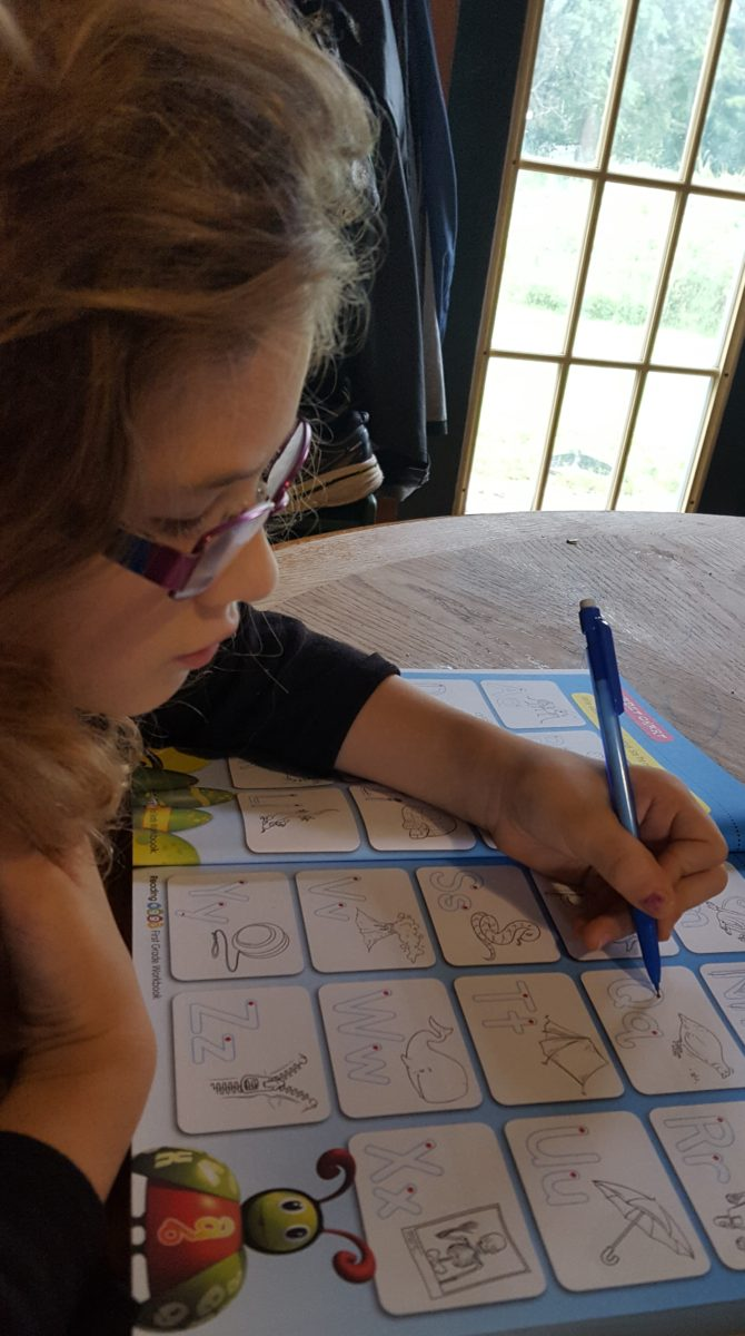 Reading Eggs workbook review girl writing her letters in a work book