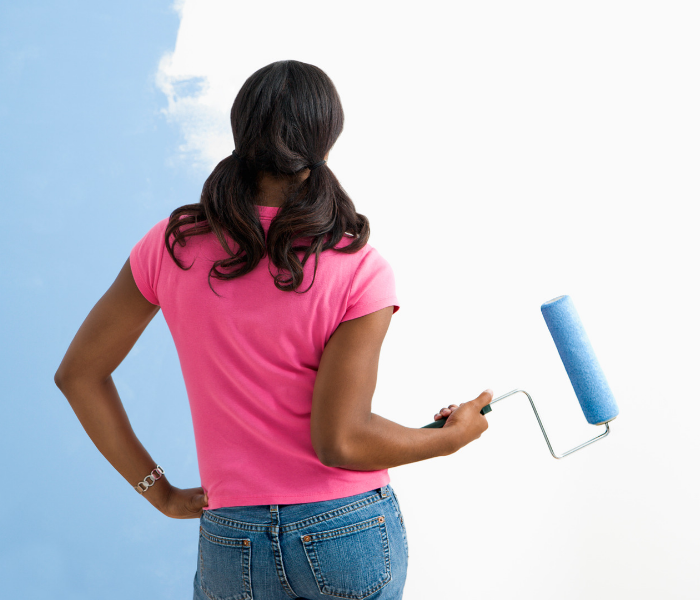 Home Improvements Eco-Friendly woman rolling volatile organic compounds blue paint on wall