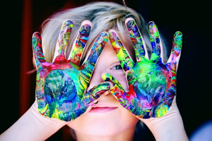Unused room child with multi-color rainbow painted hands standing in a craft room