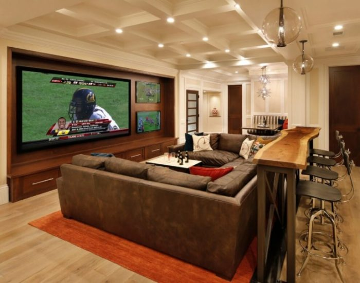 Basement into a more useful space basement family room home theater big screen tv large couch barstools