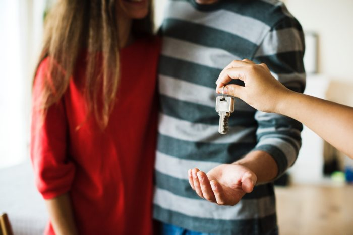 Top home-buying mistakes young couple receiving keys to first home
