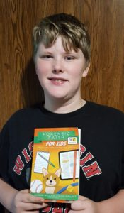Forensic Faith For Kids book being held by a teen boy