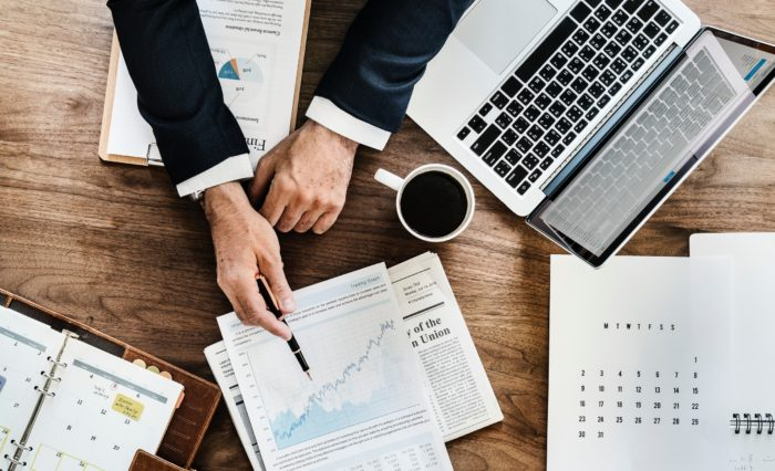 New business owners man's hands showing a business growth graph at a desk with coffee keyboard schedule