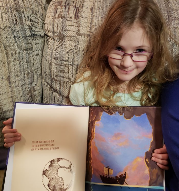 Psalm 136 book review a young girl in glasses shows the pictures in her Christian picture book