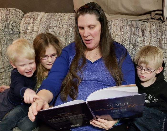 Psalm 136 book review Mom and three small children reading a christian picture book together on couch