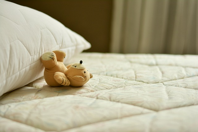 Cleaning hacks teddy bear and pillow on a mattress of a bed waiting to be remade after cleaning it