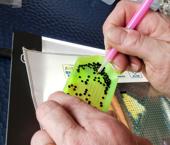 Diamond painting tutorial drill pen about to get a rhinestone from sorting tray canvas over light box