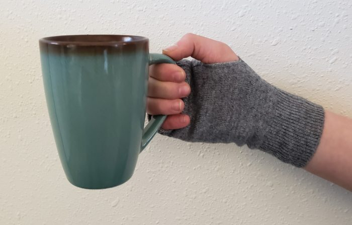 Cashmere writing gloves on a hand holding a green and brown coffee mug