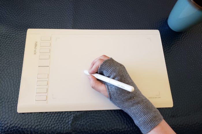 Cashmere writing gloves worn on a woman's right hand as she uses a graphics tablet drawing pen to do digital art