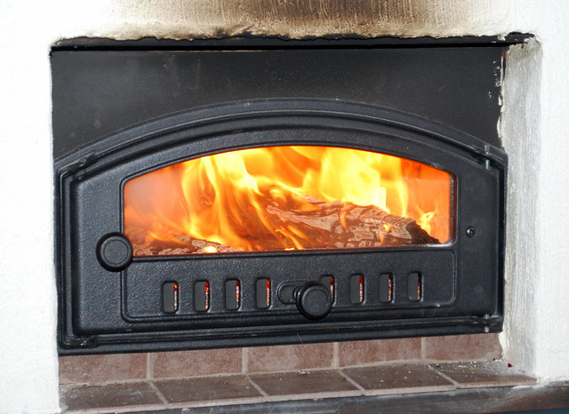 Wood burner black above stone tile fire going inside