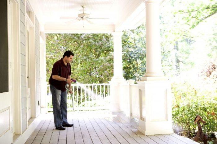 Preventative home maintenance washing and sealing porch deck man spraying hose