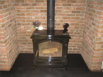 Wood burning stove with pipe brick wall behind it