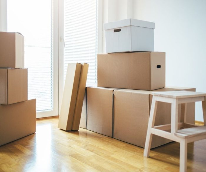 Portable metal container moving packed boxes and stool waiting in the dining room to be moved into moving crate