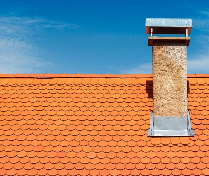 orange red shingled roof with cement block chimney