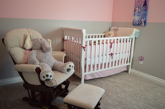 baby nursery stocked with toys linens minimal decor painted in pinks and grays