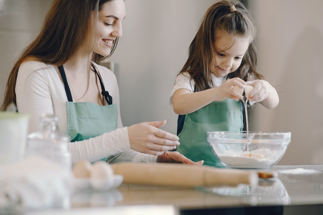 kids busy during lockdown mom daughter cracking egg over bowl baking