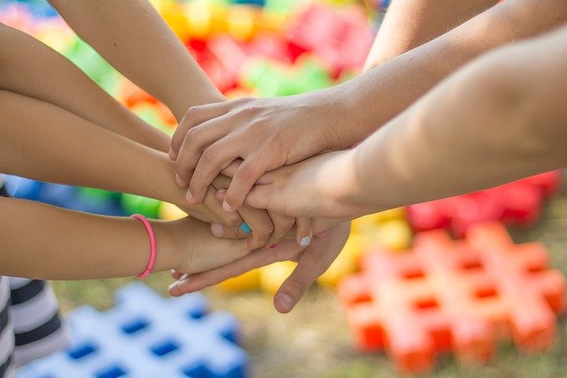 parenting is not easy family hands on top of eachother teamwork