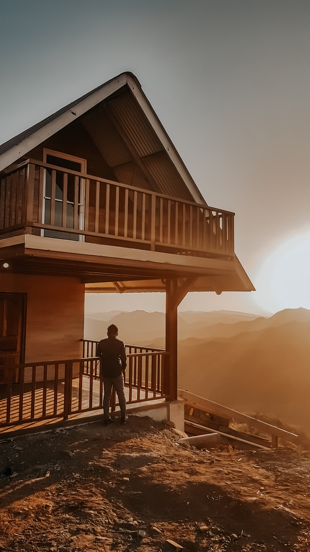 Building your house A frame cabin on top of hill silhouette of a man on porch