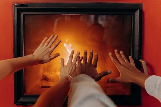 home warmer without heat on couple's hands in front of burning fire in fireplace